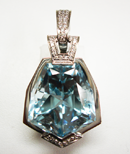 Photo of a blue Topaz gemstone in a pendant mounting which has a chip which needs to be repaired.