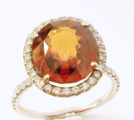 Picture of an orange Spessartite garnet in a ring which needs the table repolished.