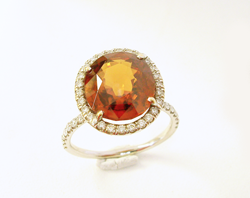 Photo of a diamond ring with an orange Spessartite Garnet center stone.
