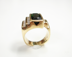 Photo of a ring with a row of Diamonds and a rectangular blue-green Tourmaline which has a scratched table.